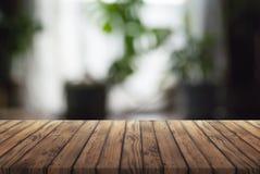 Stary drewniany reklama stół na zamazanym tle, palącej drewnianej teksturze, domowym pokoju z okno i kwiatach, fotografia royalty free