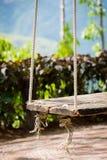 Stary drewniany rocznika ogródu huśtawki obwieszenie od wielkiego drzewa i mo Fotografia Royalty Free