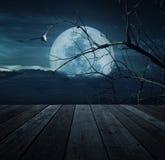 Stary drewniany stół nad ptakiem, nieżywym drzewem, księżyc i strasznym chmurnym sk, Fotografia Royalty Free