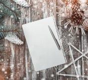 Stary drewniany tło, zielony jedlinowy drzewo z biel rożkami, kosz rożki, orzechy włoscy i dekoracyjna gwiazda, list Santa Obraz Stock