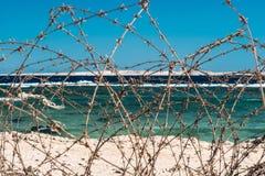 Stary drut kolczasty przed morzem Drut i niebieskie niebo z chmurami Zbawczy ogrodzenie drut kolczasty przeciw morzu i niebieskie Fotografia Stock