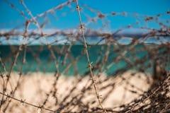 Stary drut kolczasty przed morzem Drut i niebieskie niebo z chmurami Zbawczy ogrodzenie drut kolczasty przeciw morzu i niebieskie Obraz Stock