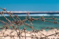 Stary drut kolczasty przed morzem Drut i niebieskie niebo z chmurami Zbawczy ogrodzenie drut kolczasty przeciw morzu i niebieskie Zdjęcie Stock