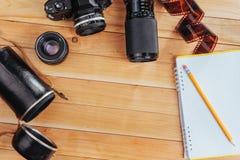 Stary ekranowy rolka notatnik z ołówkiem na drewnianym tle, kamera i film i Zdjęcia Royalty Free