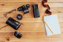 Stary ekranowy rolka notatnik z ołówkiem na drewnianym tle, kamera i film i Obrazy Stock
