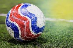 Stary futbol na zielonego oświetlenia pola sztucznym świetle na dobrze Zdjęcie Royalty Free