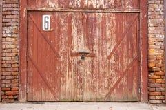 Stary garażu drzwi w białej betonowej ścianie Bramy robić drewno malujący z krakingową zieloną farbą zdjęcia royalty free