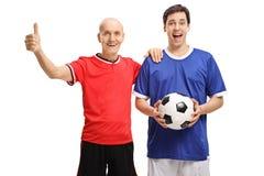 Stary gracz piłki nożnej robi kciukowi up podpisuje z potomstwo piłki nożnej śliwkami Zdjęcia Royalty Free