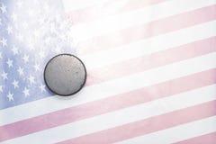 Stary hokejowy krążek hokojowy jest na lodzie z flaga amerykańską Zdjęcie Royalty Free