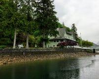 Stary hotel obok oceanu otaczającego wysokimi wiecznozielonymi drzewami w kolumbia brytyjska, Kanada fotografia royalty free