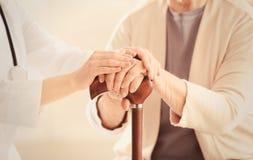 Stary i młoda kobieto trzyma ręki na chodzącym kiju zdjęcia stock
