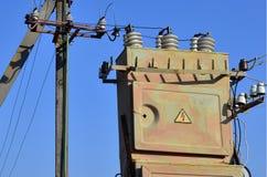 Stary i przestarzały elektryczny transformator przeciw tłu bezchmurny niebieskie niebo Przyrząd dla dystrybuci dostawa wysokość obraz royalty free