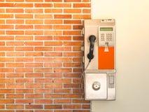 Stary jawny payphone z czerwoną ścianą z cegieł obrazy stock