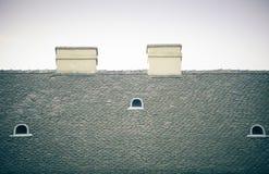 Stary kafelkowy dach z kominami i dormers na niebieskiego nieba tle Fotografia Stock