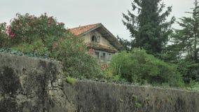 Stary kamienia ogrodzenie zaniechany wieś dom z ostrzem rozbijał butelki na wierzchołku zbiory