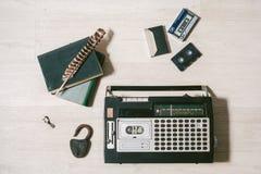 Stary kasety taśmy pisak, klucz, kędziorek, książki i piórko na drewnie, Zdjęcia Royalty Free