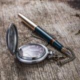 Stary kieszeniowego zegarka i fontanny pióro na drewnianym tle Obrazy Royalty Free