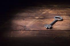 Stary klucz biały metal kłama na drewnianej powierzchni w promieniu światło obraz royalty free