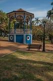 Stary kolorowy gazebo i oświetleniowy słup po środku ogródu z zielonym gazonem w słonecznym dniu przy São Manuel, fotografia stock