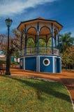 Stary kolorowy gazebo i oświetleniowy słup po środku zielenistego ogródu w słonecznym dniu przy São Manuel, obraz stock