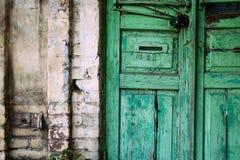 Stary krakingowy zielony drzwi z rękojeścią Malujący Ściana Z Cegieł obrazy royalty free