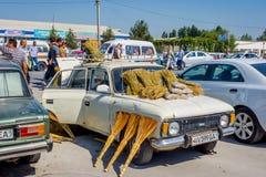 Stary Lada z miotłami dla sprzedaży, Kumtepa bazar Zdjęcia Royalty Free