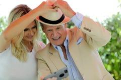 Stary mężczyzna bierze selfie z młodą kobietą dla ogólnospołecznych środków obrazy stock