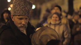 Stary mężczyzna spełnianie na etnicznym instrumencie muzycznym na zatłoczonej ulicie, cossack zbiory