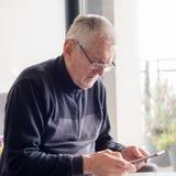 Stary mężczyzna używa mądrze telefon fotografia stock