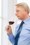 Stary mężczyzna wącha czerwone wino Fotografia Royalty Free