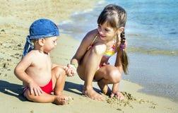 Stary młodszy brat na seashore spojrzeniu przy each inny i siostra, Zdjęcie Royalty Free