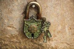 Stary metalu kędziorek i dwa klucza na tło piaskowa ścianie Fotografia Stock