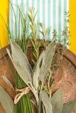 Stary miedziany naczynie z rozmaitością świezi ziele na błękitnym pasiastym fałdowym ręcznika i koloru żółtego tle fotografia stock