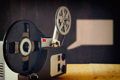 Stary 8mm Ekranowy projektor nad drewnianym stołem i textured tłem Zdjęcia Royalty Free