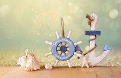 Stary nautyczny drewniany koło, kotwica i skorupy na drewnianym stole nad abstrakcjonistycznym błyskotliwości tłem, fotografia royalty free