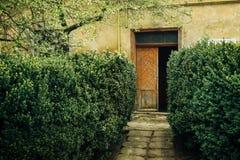 Stary nieociosany budynek z drewnianymi drzwiami i geen ogrodowego, włoch p zdjęcia royalty free
