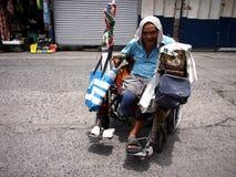 Stary niepełnosprawny mężczyzna stacza się wokoło w jego wózku inwalidzkim w jawnym rynku Obraz Royalty Free