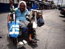 Stary niepełnosprawny mężczyzna stacza się wokoło w jego wózku inwalidzkim w jawnym rynku Zdjęcie Stock