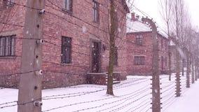 Stary ośniedziały drutu kolczastego ogrodzenie Auschwitz Birkenau koncentracja i eksterminacja obozujemy Cegła koszaruje w spada  zdjęcia stock