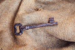 Stary ośniedziały klucz dla skarbu sekretu na rocznik jutowej tkaninie Obrazy Royalty Free