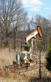 Stary ośniedziały nafciany benzynowego well pumpjack za drutu kolczastego ogrodzeniem fotografia stock