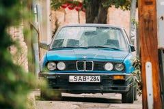 Stary ośniedziały sedan samochodowy BMW 3 serii E30 parking na ulicie BM Zdjęcie Stock