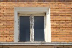 stary okno z drewnianą ramą która potrzebuje odświeżanie na ceglanym domu Zdjęcie Stock