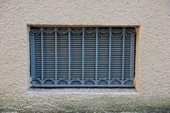 Stary okno z szarego żelaza grillem na brown betonowej ścianie zdjęcie stock