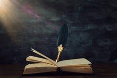 Stary piórkowy dutka atramentu pióro z inkwell i stare książki nad drewnianym biurkiem przed czernią izolujemy tło Konceptualna f fotografia stock