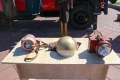 Stary pożarniczy wyposażenie, ogienia brązowy ochronny hełm i górnika ` s lampiony na stole, obrazy royalty free