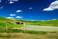 Stary pokrywający strzechą z słomą nad stawem w polach Fotografia Stock