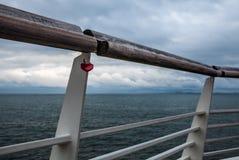 Stary poręcz przeciw północnemu morzu z kędziorkiem w formie serce Obraz Stock