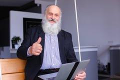 Stary przechodzić na emeryturę mężczyzna używa laptop i komunikuje z kolegi beh Fotografia Stock
