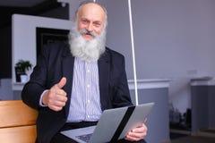 Stary przechodzić na emeryturę mężczyzna używa laptop i komunikuje z kolegi beh Obraz Stock